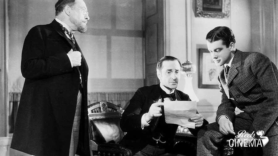 El perro de los Baskerville. Mortimer (Lionel Atwill) y Henry Baskerville (Richard Green) rodean a Sherlock